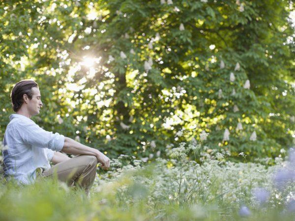 Man meditating in field of flowers