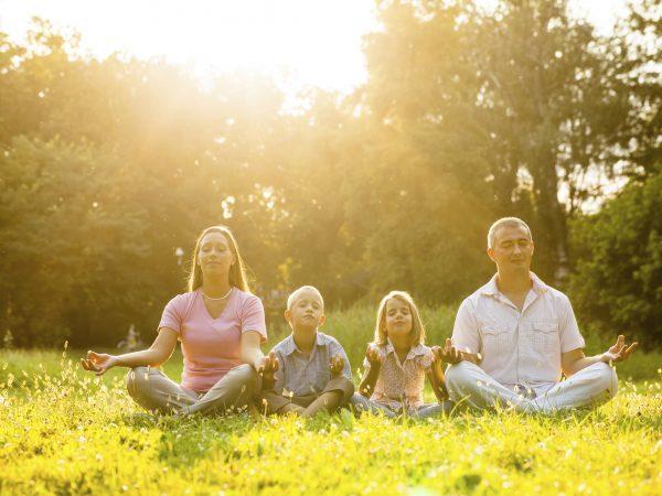 Family doing yoga in park